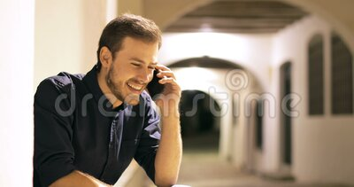 Happy man talking on phone sitting in the night. Happy man talking on mobile phone sitting in the street in the night stock footage