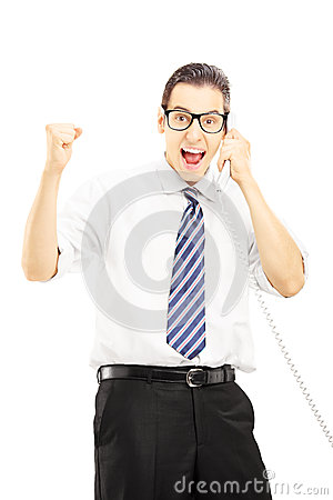 Happy man talking on a telephone and gesturing happiness