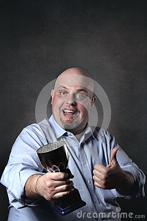 Happy man with thumb up and winner cup