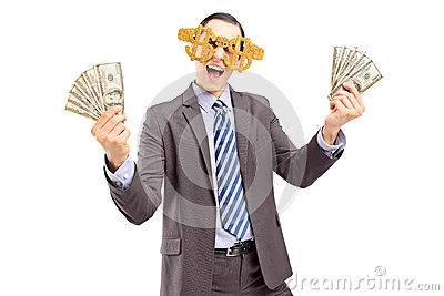 A happy man wearing dollar sign glasses and holding US dollars