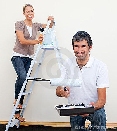 Happy man and woman decorating a room