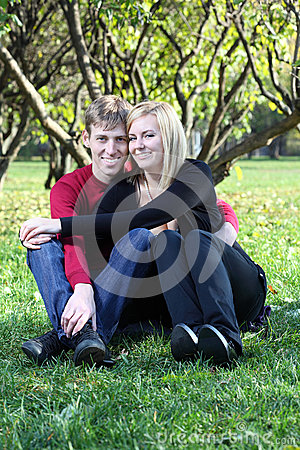 Happy man and woman embrace and sit on green grass