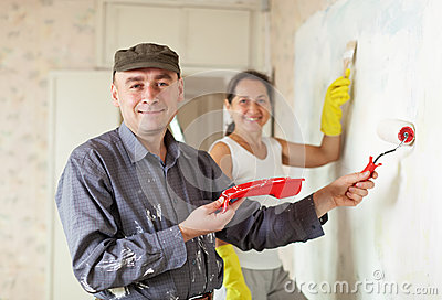 Happy man and woman paints wall at  apartment