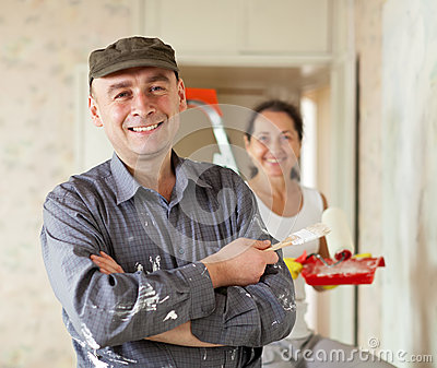 Happy man and woman paints wall at home
