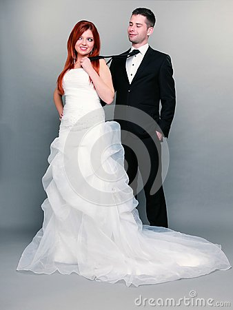 happy married couple bride groom gray background wedding day portrait red haired full length woman pulling mans tie 34638029