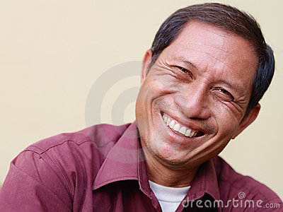 Happy mature Asian man smiling at camera