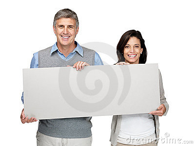 Happy mature couple  holding a blank board