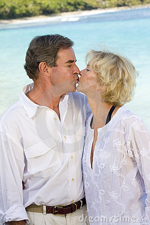 A happy mature couple kisses at the beach