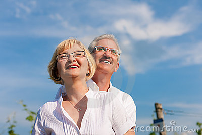 Happy mature couple looking to the blue sky