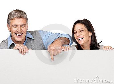 Happy mature couple pointing at blank billboard