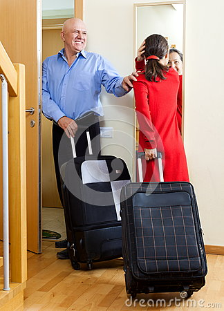 Happy mature couple with suitcases looking in mirror