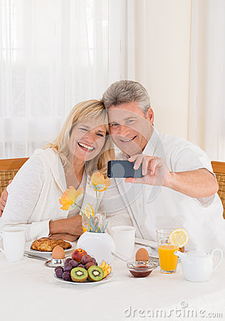 Happy mature couple taking a selfie photo on their mobile phone while having healthy breakfast