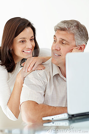 Happy mature couple using internet on laptop