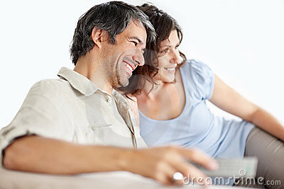 Happy mature couple watching television together