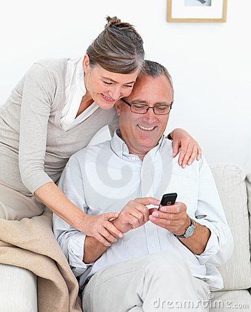 Happy mature couple writing sms together