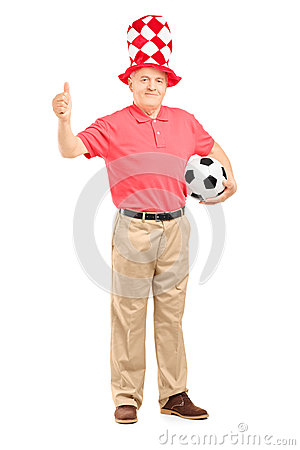 Happy mature fan with hat holding a soccer ball and giving a thu