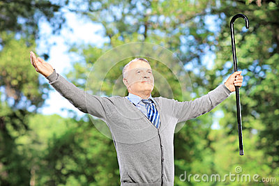 Happy mature man with cane spreading his arms