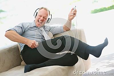 Happy mature man enjoying music on an mp3 player