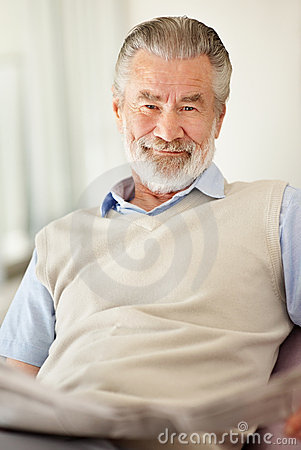 Happy mature man looks at you as he holds a newspa