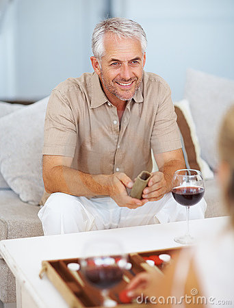 Happy mature man playing backgammon with friend