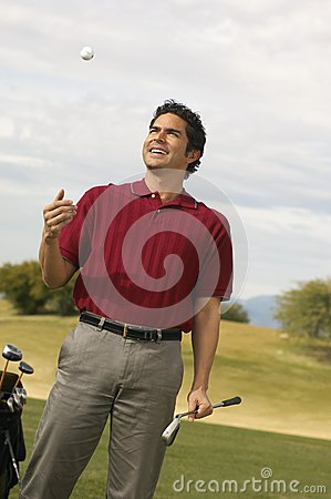 Happy Mature Man Tossing Golf Ball