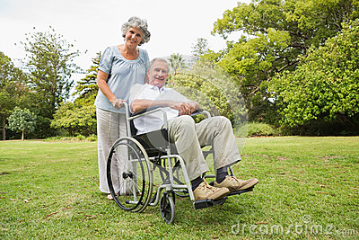 Happy mature man in wheelchair with partner