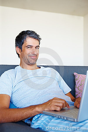 Happy mature man working on a laptop at home