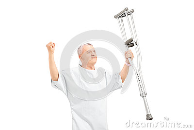 A happy mature patient holding crutches and gesturing happiness