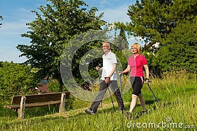 Happy mature or senior couple doing Nordic walking