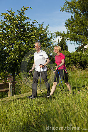 Happy mature or senior couple doing Nordic walking