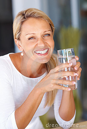 Happy mature woman holding a glass of water