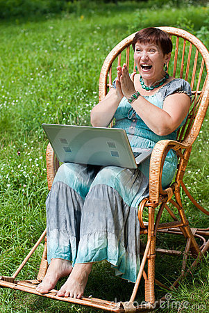 Happy mature woman with laptop in rocking chair