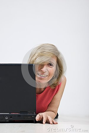 Happy mature woman with laptop on wooden floor