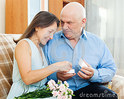 Happy mature woman looking jewel  from husband