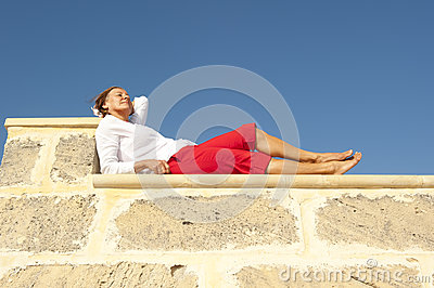 Happy mature woman lying on wall