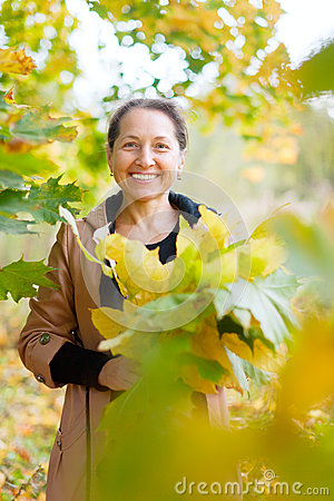 Happy mature woman with maple posy