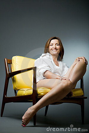 Happy mature woman relaxing on chair.