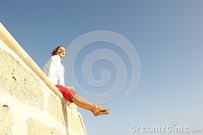 Happy Mature woman sitting on wall
