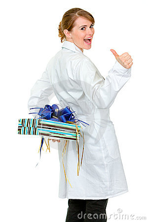 Happy medical doctor woman holding gift behind her