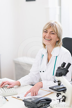 Happy middle age doctor woman at work
