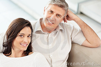 Happy middle aged couple relaxing on a couch