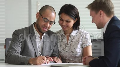 Happy mixed ethnicity couple signing bank loan contract handshake manager. Happy mixed ethnicity couple clients customers signing bank loan contract paper stock footage