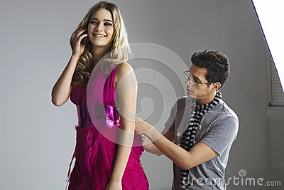 Happy model using cell phone while male designer adjusting her dress in studio