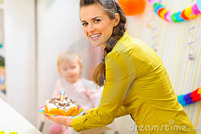Happy mom carries birthday cake for baby