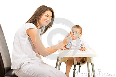 Happy mom feeding toddler boy with yogurt