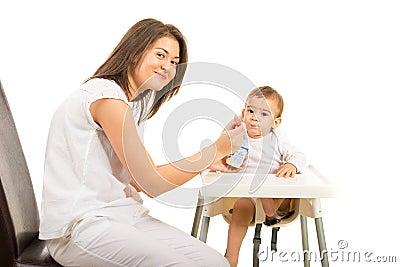 Happy mom feeding toddler boy with yogurt