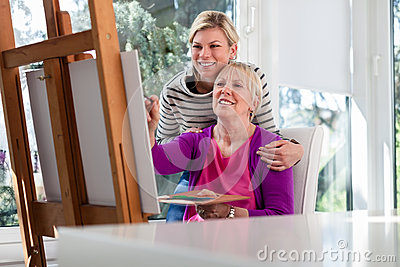 Happy mom painting and daughter smiling