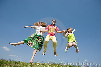 Happy Mom and two daughter jumping on meadow