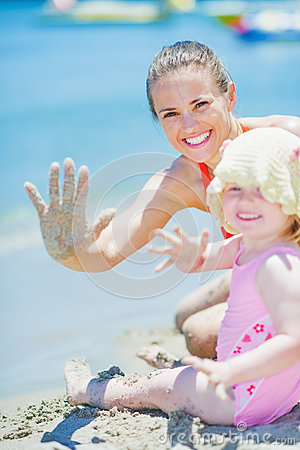 Happy mother and baby on beach greeting