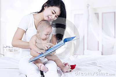 Happy mother and baby reading a book